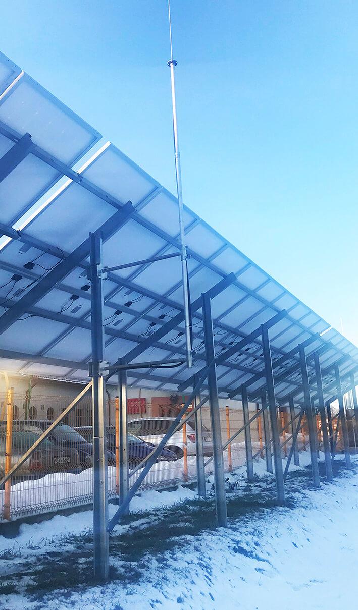 Ochrona paneli fotowoltaicznych na gruncie za pomocą masztu odgromowego izolowanego mocowanego do konstrukcji z wysokonapięciowym przewodem odprowadzającym.