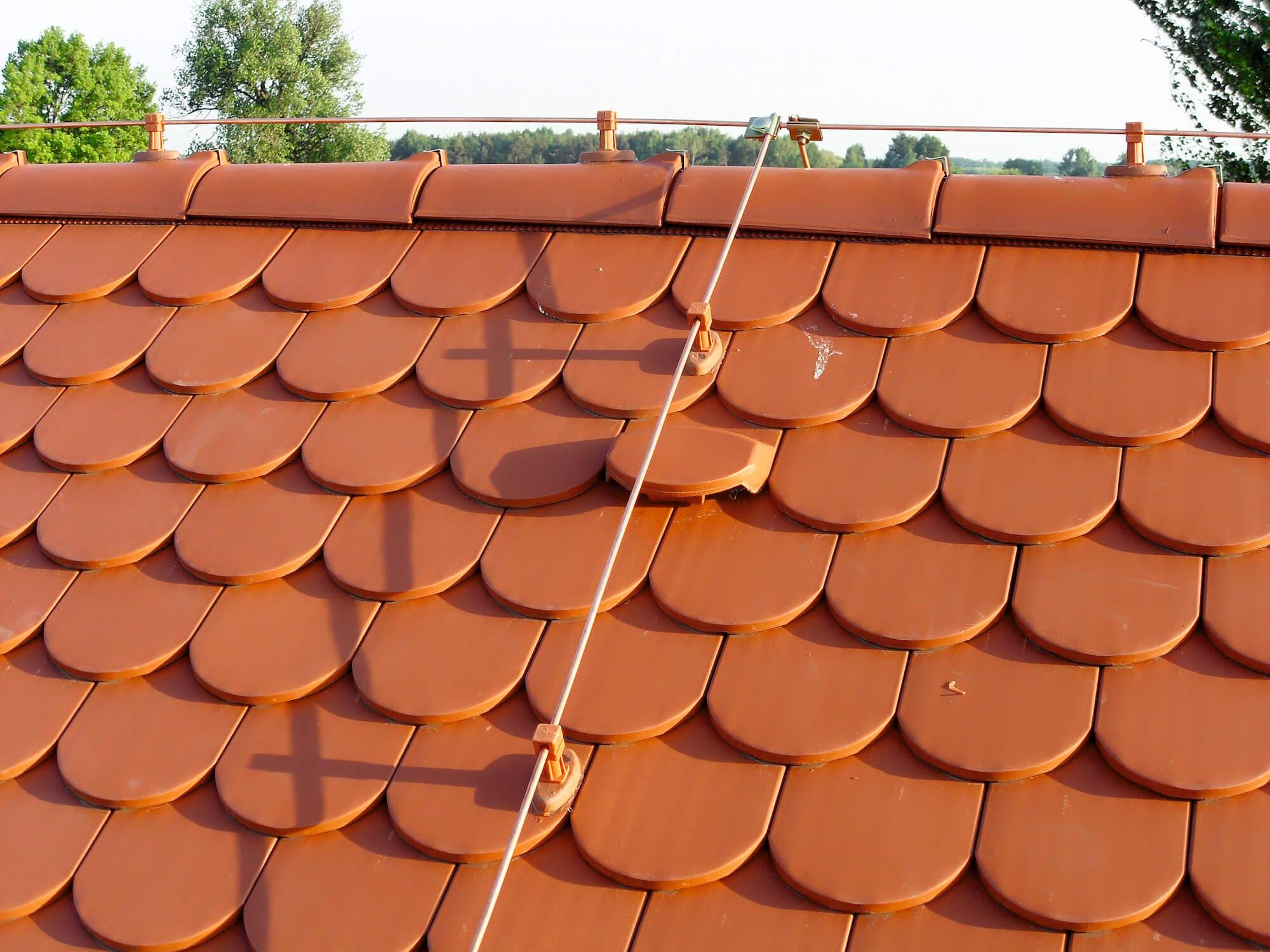 Drut miedziany prowadzony na uchwytach przyklejanych ceramiczno-plastikowych do dachu krytym dachówką ceramiczną.