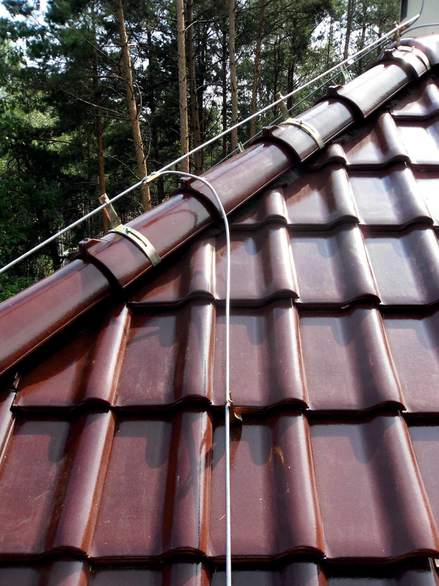 Drut FeZn prowadzony na uchwytach gąsiorowych i dachówkowych na dachu krytym dachówką ceramiczną.
