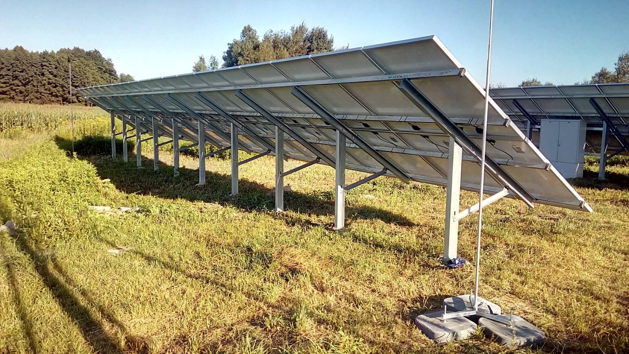 Ochrona paneli fotowoltaicznych na gruncie za pomocą masztów odgromowych z obciążnikami betonowymi na podstawie trójnożnej.